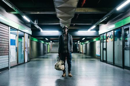 Young handsome afro black man in a underground station looking in camera, holding a bag, serious - pensive, thoughtful, travel concept Stockfoto