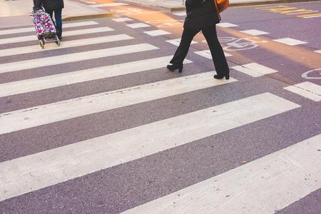 Pedestrian crossing sing with people walking on it