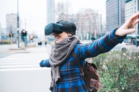 viewer: Young handsome caucasian woman using 3D viewer outdoor in the city smiling with arms wide open - happiness, futuristic, technology concept