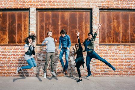 美しい民族青年と女性の友人・ シティの屋外ジャンプ楽しんで幸福、友情、チームワークの概念のグループ