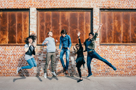 multi racial group: Group of young beautiful multiethnic man and woman friends having fun jumping outdoor in the city - happiness, friendship, teamwork concept Stock Photo