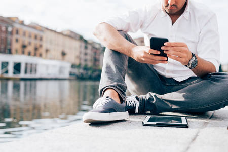 Young beautiful caucasian man, sitting on the riverbank, using smart phone hand hold - technology, social network, happiness concept