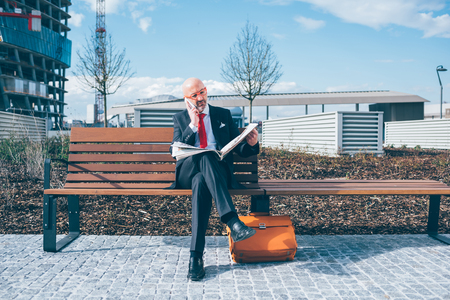 Middle-aged contemporary businessman sitting on a bench outdoor in the city reading newspaper talking smart phone - work, conversation, information concept Stockfoto