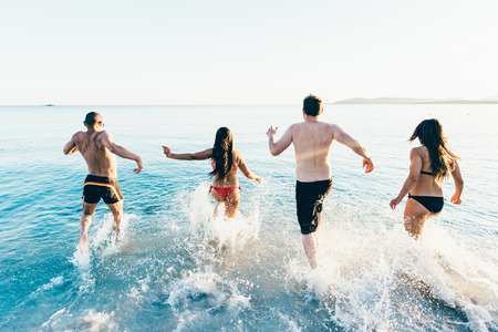 authentic: Rear view of a group of young multiethnic friends women and men running on the beach to the sea in summertime - happiness, summer, friendship concept