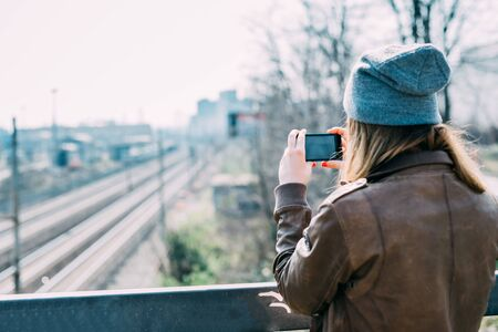 Rear view of young beautiful blonde hipster woman in the city using smartphone taking photograph - technology, social network, communication concept Stockfoto