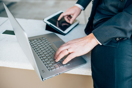 Close up on the hands of middle age caucasian businessman using technological devices like notebook leaning on his knee and tablet - business, work, multitasking concept
