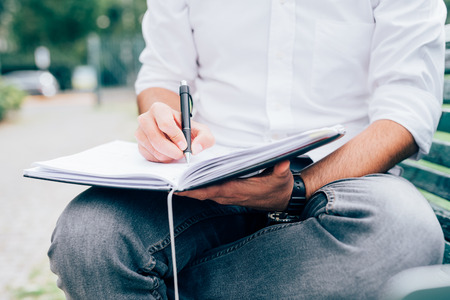 Close up on the hands of a young man writing on his agenda - business, planning, appointment concept Stockfoto