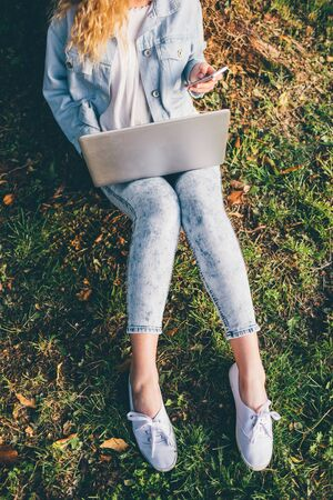 From the neck down view of young blonde woman sitting ont he grass using notebook and smart phone hand hold - technology, multitasking, social network concept Stockfoto