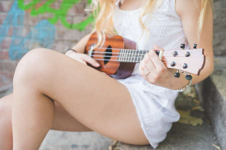 millennial: Close up hand young millennial caucasian woman playing ukulele - music, song, chord concept