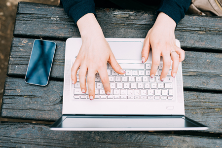 tapping: Top view of the hands of a woman tapping the keyboard of a laptop on a wooden desk with smart phone leaning near - technology, multitasking, business concept
