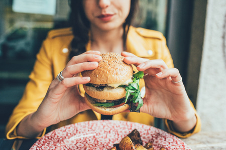 Close up on the hands of a young woman sitting holding an hamburger - hunger, food, meal concept