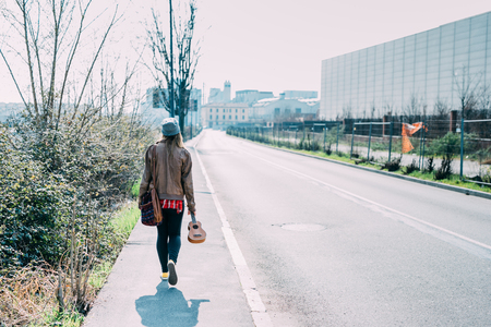 Back view of young beautiful caucasian woman walking down the road holding ukulele - future, composer, traveler concept Stockfoto
