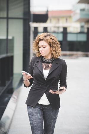 Knee figure of a young beautiful caucasian contemporary businesswoman walking through the city using smartphone and tablet looking the screen- technology, network, business, finance concepts Stockfoto
