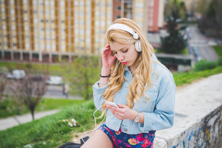 Young blonde caucasian girl listening music with headphones and smart phone hand hold in the suburbs - technology, music, relax concept Stockfoto