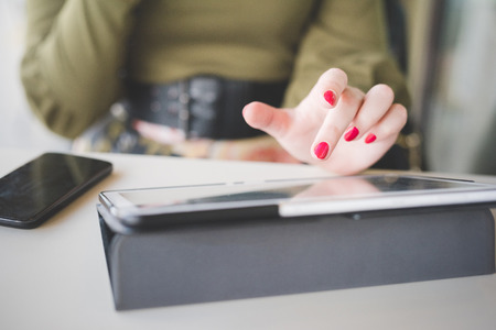Close up on the hand of a young handsome caucasian girl using technological devices like tablet, tapping the screen - multitasking, technology concept Stockfoto