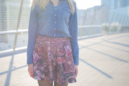 Young handsome caucasian girl posing in the street - detail of the dress composed by a floral skirt, a pair of black shoes and a jeans shirt