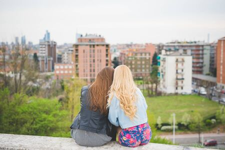 Two young multiethnic woman blonde and brunette from behind sitting with city in background - best friends, friendship concept