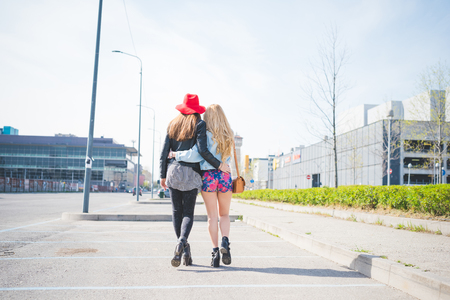 Back view two beautiful blonde and brunette multiethnic friends walking through the city hugging and having fun - friendship, emancipation concept