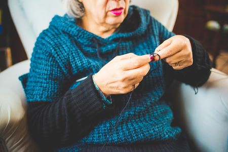 Hands of a woman knitting with knitting needles and woolen yarn, filtered vintage - handcraft, hobby concept Stockfoto