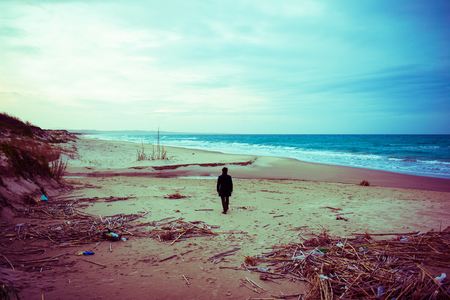 A solitary man walks along a sandy beach in winter with garbage and wood, copy space on top and bottom