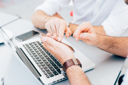Close up on the hands of two men using technological devices, tapping the screen of a tablet hand hold - technology, communication, multitasking concept Stockfoto