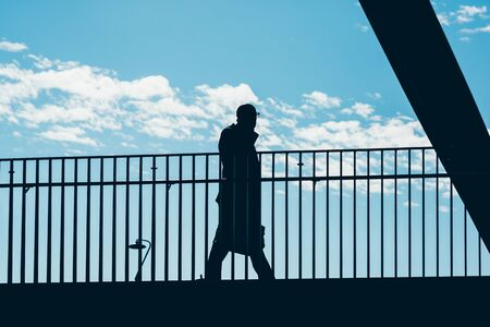Silhouette of businessman in shadow walking outdoor stand out a blue sky - business concept