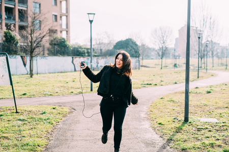 Young beautiful caucasian indie woman with septum piercing outdoor in a city park in back light listening music with headphones and smart phone hand hold dancing - dancing, music, relaxing concept