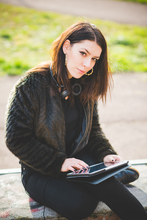 Young beautiful caucasian indie woman with septum piercing using tablet outdoor in city back light, looking at camera smiling - serene, technology, social network concept