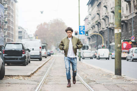 Young handsome cauciasain curly hair man walking in the street of the city, talking smartphone, overlooking pensive - communicaiton, technology, thoughtful concept Stockfoto