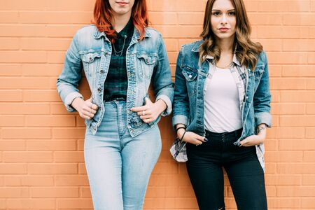 From the neck down view of two fashionable women leaning on a brick wall, wearing jeans clothes, with hands in pocket Stockfoto