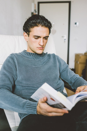 Young handsome caucasian man sitting on the armchair in his house, looking downward reading a book - student, knowledge, culture concept