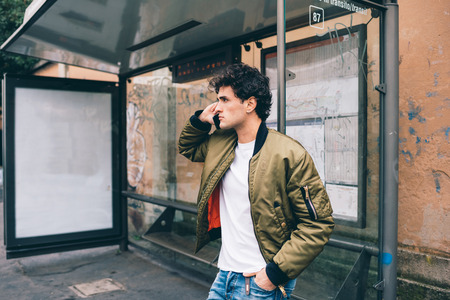 Young handsome caucasian man leaning on a bus stop talking smart phone while waiting - technology, social network, communication concept