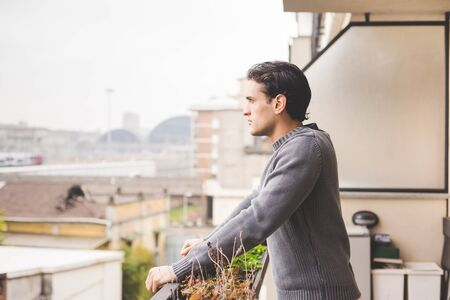 Half length of young handsome man standing on a balcony outdoor, overlooking, pensive - serious, thoughtful, thinking future concept