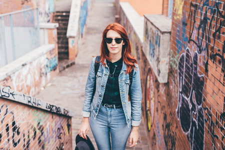 Knee figure of young handsome caucasian redhead straight hair woman posing on a staircase in the city, wearing sunglasses, looking in camera pensive - serious, thoughtful concept Stockfoto