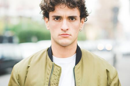 Portrait of young handsome caucasian brown curly hair man posing outdoor in the city, looking in camera, serious - pensive, thoughtful, thinking future concept