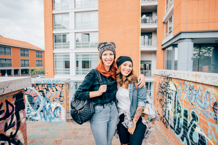 Knee figure of two young handsome caucasian blonde and redhead straight hair women walking hugging outdoor in the city, laughing, looking in camera - having fun, carefree, youth concept Stockfoto