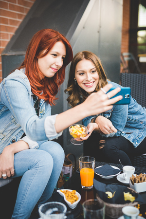 Two young handsome caucasian blonde and redhead straight hair women sitting in a bar taking a selfie with smartphone - technology, social network, vanity concept