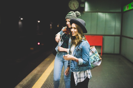 Knee figure of two young handsome caucasian blonde and redhead straight hair women waiting in the underground for tube, one using smartphone - transport, technology concept