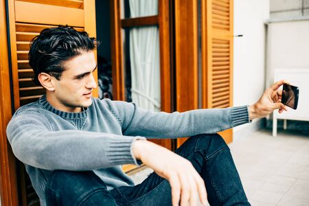 Young handsome caucasian brown hair man sitting on the balcony outdoor in his house, using smart phone taking selfie - technology, social network, communication concept