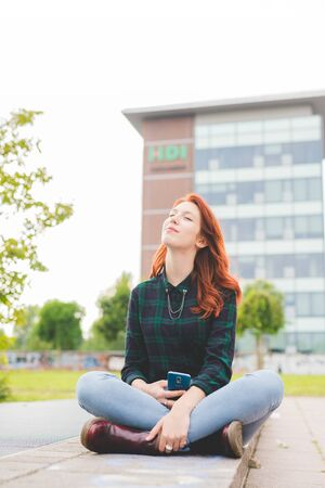 Young beautiful redhead woman sitting leg crossed in the city, holding a smartphone, looking over eyes closed serene - technology, social network, serenity concept