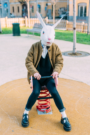 Young beautiful asian hipster woman in the city wearing rabbit mask in a playground- carnival, halloween, crazy concept