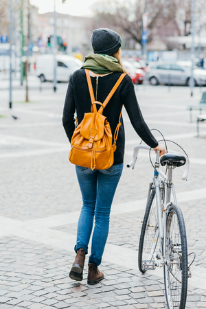 Rear view of young beautiful caucasian woman with backpack, holding bike