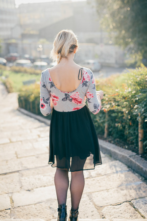 From behind view of young beautiful blonde woman walking outdoor in the street of the city