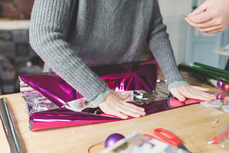 Close up on the hands of young woman wrapping christmas present with wrapping paper