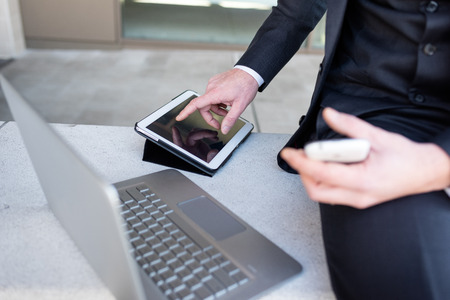Close up on the hand of multitasking businessman using tablet, computer and smart phone
