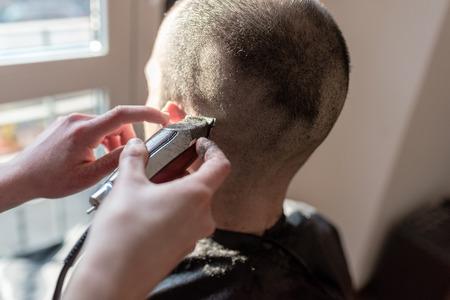 Close up on woman barber hand cutting hair using razor Zdjęcie Seryjne