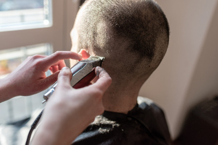 Close up on woman barber hand cutting hair using razor Stockfoto