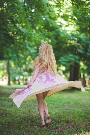 young beautiful caucasian blonde long hair woman dancing in the forest wearing long pink dress Stockfoto