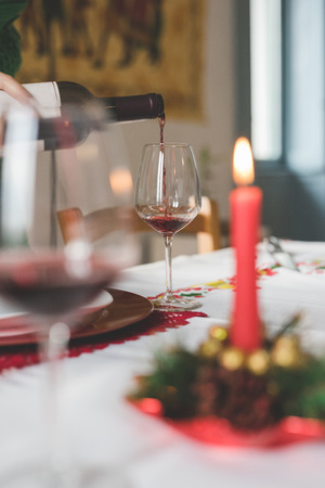 Close up on a hand pouring a glass with red wine on a table set for christmas