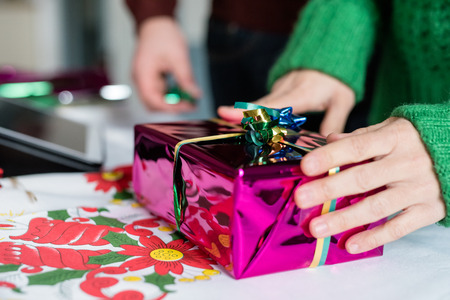 Close up on the hand of a young woman wrapping a christmas present, using scissor to make ribbon out of string